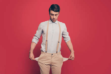 Photo for Professional, cunning magician, illusionist, gambler in casual outfit, showing two empty pockets out, standing over red background, looking down - Royalty Free Image