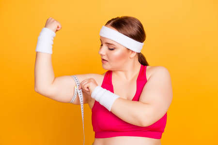 Close up portrait of confident concentrated sportive fatty woman wearing pink top and sweat-band, she is measuring her upper arm using tape measure