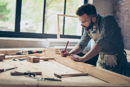Photo pour Side profile view photo of hardworking busy professional confident cabinet maker taking measure of wooden plank with a pencil near other instruments - image libre de droit
