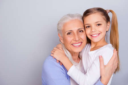 Close up portrait of cute small lovely granddaughter and her charming nice kind granny they are hugging isolated on gray background copy-space