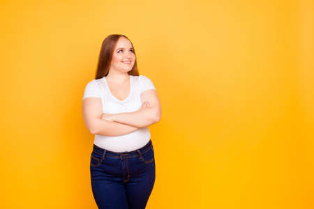 Happy cheerful joyful confident with chubby face oversize woman wearing casual tshirt and dark blue jeans, standing with folded arms, looking at empty blank space