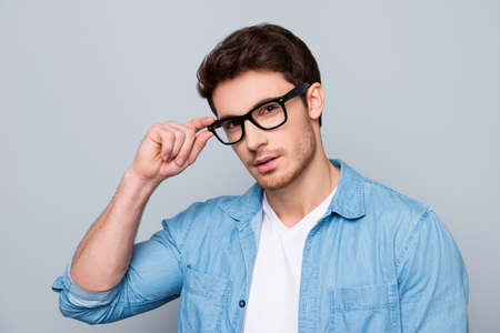 Foto de Portrait of stunning, brutal, sexy, concentrated, cool man in jeans shirt holding eyelet of glasses on his face with fingers, looking at camera, isolated on grey background - Imagen libre de derechos
