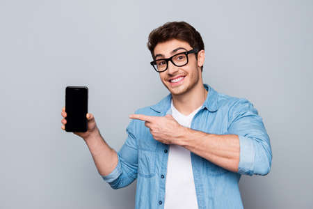 Photo pour Portrait of cheerful, positive, attractive guy with stubble in jeans shirt, having smart phone with black screen in hand, pointing with forefinger to product - image libre de droit