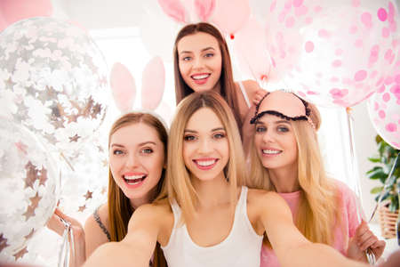 Self portrait of pretty, attractive, charming, cheerful, funny, cute girls shooting selfie on front camera enjoying meeting indoor, celebrating event with air balloons, having rabbit ears and eye mask