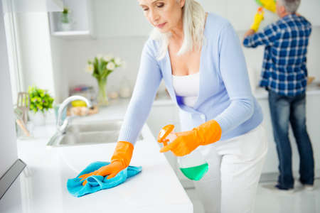 Hygiene concept, cropped portrait of cleanly neat serious woman in protective gloves using, holding spray in hands rubbing tabletop with rag, man helping her on blurred background in flat, apartment