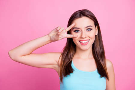 Close up portrait of cute sweet lovely modern  attractive tender gentle gorgeous with flawless ideal skin perfect makeup girl demonstrating two fingers near an eye, isolated on bright pink background