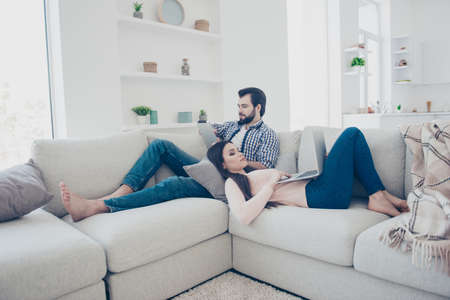 Portrait of attractive stylish couple having holding electronic devices in hands checking email chatting with friends searching information, using wi-fi internet