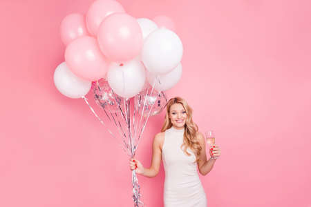 Foto de Portrait of pretty charming girlfriend having air balloons and sparkling wine beverage in hands looking at camera isolated on pink background - Imagen libre de derechos