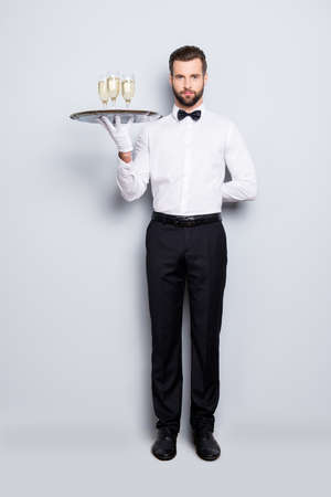 Photo for Full size fullbody portrait of concentrated man in classic white shirt and black bowtie holding hand behind the back and tray with three glasses of sparkling wine, isolated on grey background - Royalty Free Image