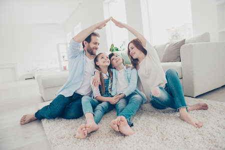 Photo pour New building residential house purchase apartment concept. Stylish full family with two kids sitting on carpet, mom and dad making roof figure with hands arms over heads - image libre de droit
