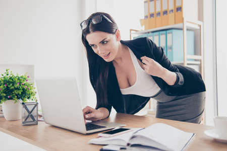 Portrait of charming sexy woman bending over near desktop showing her big tits boobs decollete open jacket having video-call with lover