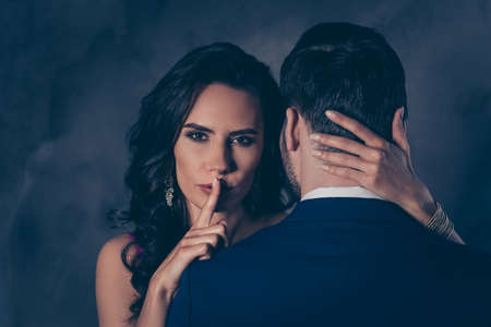 Shh! Portrait of tempting brunette lady showing silence sign with forefinger touching secret mysterious gentlemen with rear view, lovely Mr and Mrs isolated on grey background