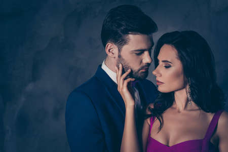 Photo pour Portrait of naughty romantic couple looking at each other gentle touch, pretty charming brunette lady harsh bearded hispanic gentlemen isolated on grey background with copy space. Intimacy concept - image libre de droit