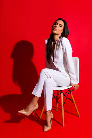 Posing snap portrait of cool hot woman in white suit sitting on chair looking at camera isolated on bright red background. Photoshooting studio concept