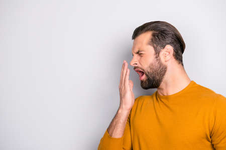 Photo pour Side profile half-faced portrait of tired sleepy bored handsome bearded unhappy with trendy hairdo guy yawning covering mouth with hand isolated on gray background copy-space - image libre de droit