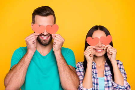 Foto de Portrait of creative joyful couple closing eyes with small paper carton red hearts isolated on vivid yellow background. Fall in love story true feelings concept - Imagen libre de derechos