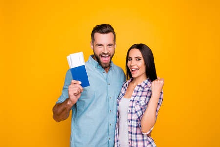 Portrait of successful lucky couple getting visa abroad holding raised fist showing passport with flying tickets shouting with wide open mouth isolated on vivid yellow background