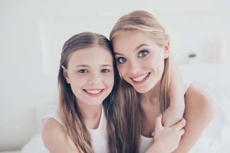 Foto de Close up portrait family photo of cute sweet lovely beautiful charming glad cheerful with toothy beaming smile mum and her pretty daughter embracing neck spending time together domestic life - Imagen libre de derechos
