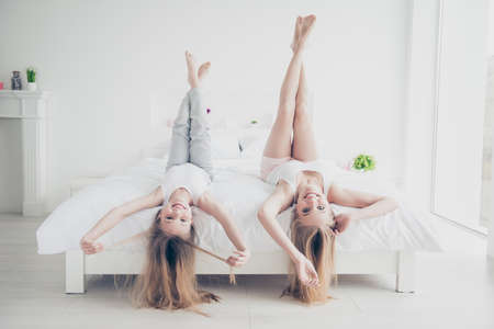 Foto de Adult mom mommy mum motherhood emotion expressing delight rejoice concept. Pretty funny laughing funky beautiful cute lovely girls lying upside down on bed touching long healthy hairstyle - Imagen libre de derechos
