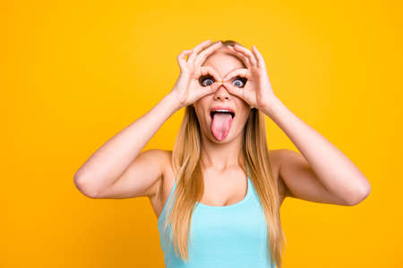 Foto de Funny and cheerful girl with long blond straight hair. Female showing gesturing ok sign with her two hands like a glasses and looking at camera, demonstrating tongue out and opened eyes wide - Imagen libre de derechos