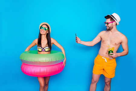 Photo pour Guy in the hat, sunglasses and bright shorts holding a cool cocktail and taking pictures of a happy girl with multi-colored inflatable circles on the smartphone - image libre de droit