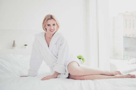 Foto de Young cute smiling blonde woman in bed on white sheets and blanket wearing white bathrobe in bedroom with white interior. Healthcare - Imagen libre de derechos