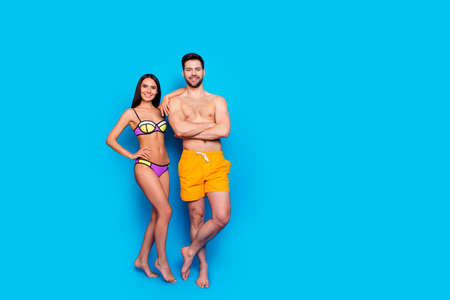 Foto de Full-length shot with slim girl in a separate swimsuit laid her hand on shoulder to guy in yellow shorts. The concept of summer vacation, isolated image on a blue background with copy space - Imagen libre de derechos