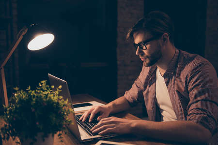 Portrait of attractive programmer, hard worker, busy man in shirt with hairstyle working at night, taking work at home, looking at screen of laptop, sitting in work station, holding hands on keypad