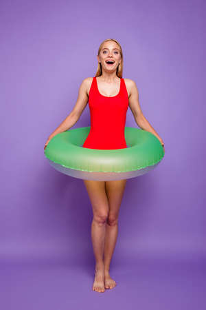 Photo pour Finally, long-awaited sea! Full-size portrait of blond girls with green life buoy at the waist look enthusiastically forward isolated on purple background - image libre de droit