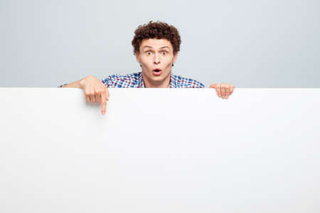 Photo pour Cheerful young man standing behind the white blank banner and pointing down at a white copyspace isolated on light gray background - image libre de droit