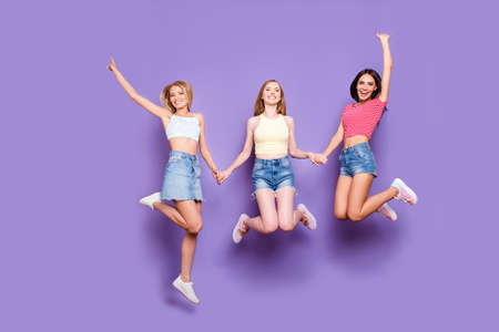 Photo pour Portrait of foolish playful girls holding hands jumping in air enjoying vacation celebrating achievement isolated on vivid violet background - image libre de droit