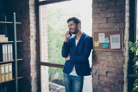 Attractive handsome young brunet bearded smiling executive worker man in office work station work place, talking on the phone