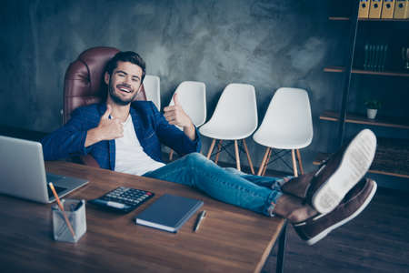 Attractive handsome young brunet bearded executive worker smiling man in office work station work place, sitting in chair, legs lying on table, dreaming, showing thumbs up