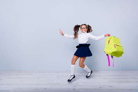 Foto de Back to school concept. Full length, legs, body, size portrait of cheerful, cute, nice, lovely, sweet girl in blue skirt, white blouse and yellow rucksack jumping isolated on light gray background - Imagen libre de derechos