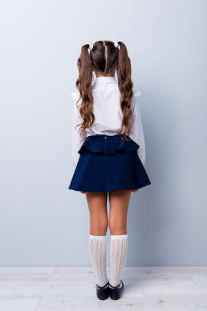 Snap shot rear back view of nice adorable stylish girl with curly pigtails in formal white blouse shirt, short blue skirt, gaiters, shoes. Isolated over grey backgroundの写真素材