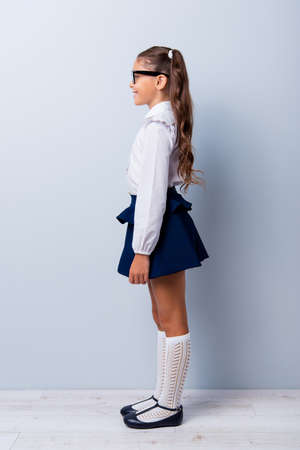 Snap shot profile side view of nice cute cheerful adorable lovely stylish small girl with curly ponytails in white formal blouse shirt, short blue skirt, gaiters. Isolated over grey backgroundの写真素材