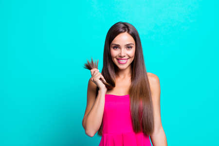 Photo for Close up photo portrait of glad nice pretty satisfied lady holding in hand showing healthy ends isolated on bright blue background - Royalty Free Image