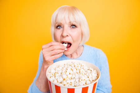 Photo pour Old woman with holding a bucket of popcorn and watching exciting - image libre de droit