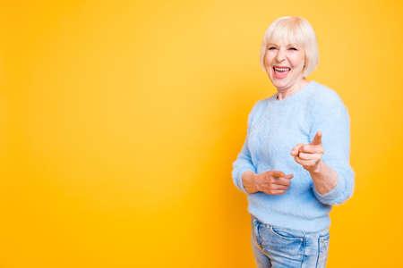 Foto de Portrait of confident modern granny pointing two index fingers a - Imagen libre de derechos