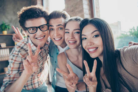 Photo for Self-portrait of four cheerful glad adorable people, handsome nerd guys and beautiful attractive girls having rest, pause, break, showing v-signs at work, meeting, gathering, diversity - Royalty Free Image