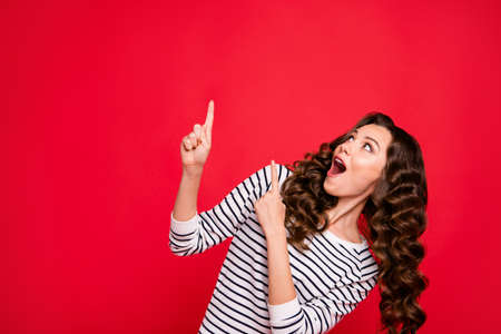 Foto de Close up portrait of beautiful cute attractive she her girl shocked oh yeah yes cool selling with finger in top of empty space wearing white sweater outfit isolated on red vivid bright background - Imagen libre de derechos