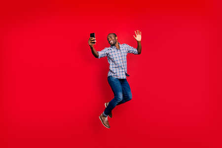 Photo for Full length body size of nice funny crazy handsome cheerful optimistic guy wearing checkered shirt holding in hands cell waving hi hello isolated on bright vivid shine red background - Royalty Free Image