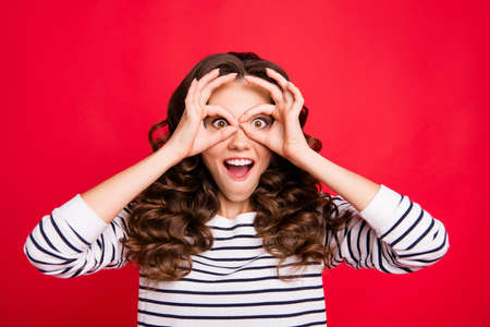 Photo pour Close up portrait of attractive gorgeous charming she her girl  brunette hands in specs form near eyes long wave hair lying on shoulders white striped pullover isolated on red bright vivid background - image libre de droit