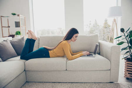 Foto de Profile side view portrait of nice lovely attractive charming calm peaceful focused clever smart straight-haired girl lying barefoot on divan preparing homework task email in light interior room - Imagen libre de derechos