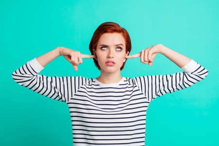 Foto de Portrait of nice pretty charming attractive sad red-haired lady wearing striped pullover rolling eyes up closing ears with forefingers isolated over bright vivid shine green turquoise background - Imagen libre de derechos