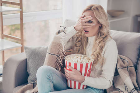 Photo pour Portrait of nice attractive stylish funny astonished stunned wavy-haired lady housewife wearing sweater sitting on divan holding in hands corn box watching video opened mouth in light interior room - image libre de droit