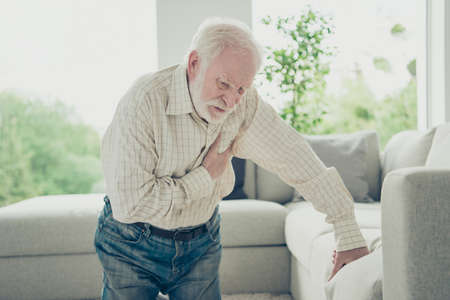 Photo pour Sad tired stylish old man wearing checked shirt leaning on divan - image libre de droit