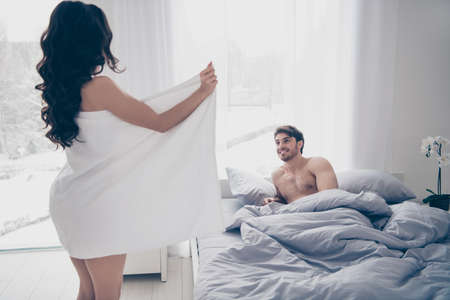 Photo pour A woman in white towel flashing her body to her husband lying on the bed. side view - image libre de droit