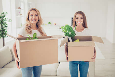 Photo pour Close up photo two people mum and teen daughter with paper big boxes in arms ready to change decor do repair wear white t-shirts jeans in bright flat stand in front of comfortable sofa - image libre de droit