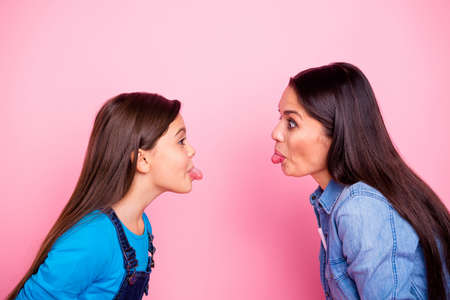 Photo pour Profile side view portrait of two nice cute crazy lovely attractive cheerful cheery positive straight-haired girls showing tongue out mood bad behavior isolated over pink pastel background - image libre de droit